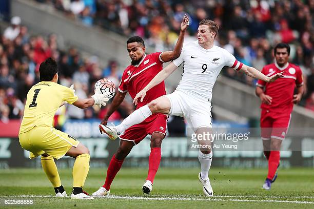 Chris Wood of New Zealand competes against goal keeper Thomas Schmidt and defender Emile Bearune of New Caledonia during the 2018 FIFA World Cup...