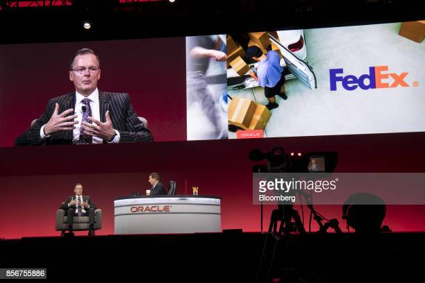 Chris Wood vice president of transformation at FedEx Corp left speaks as Mark Hurd chief executive officer of Oracle Corp listens during the Oracle...