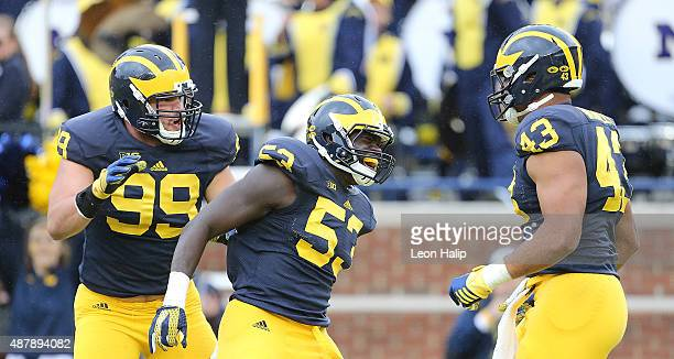 Chris Wormley of the Michigan Wolverines celebrates the sack on quarterback Marcus McMaryion of the Oregon State Beavers with teammates Matthew Godin...