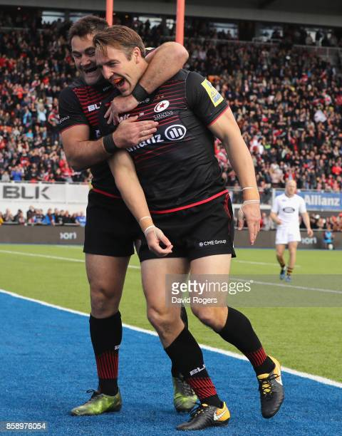 Chris Wyles of Saracens celebrates with team mate Brad Barritt after scoring the first try during the Aviva Premiership match between Saracens and...