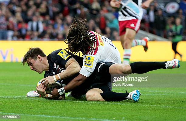 Chris Wyles of Saracens slides over despite the tackle from Marland Yarde of Harlequins to score his team's fourth try during the Aviva Premiership...