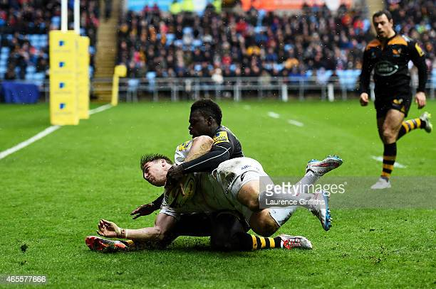 Chris Wyles of Saracens slides over to score his team's try despite thye tackle from Christian Wade of Wasps during the Aviva Premiership match...