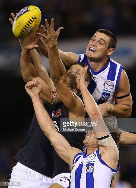 Chris Yarran of the Blues and Nathan Grima of the Kangaroos contest for the ball during the round 17 AFL match between the North Melbourne Kangaroos...