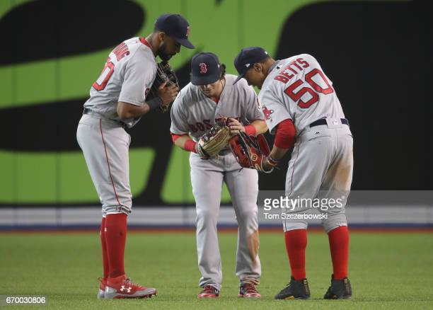 Chris Young of the Boston Red Sox celebrates their victory with Andrew Benintendi and Mookie Betts during MLB game action against the Toronto Blue...