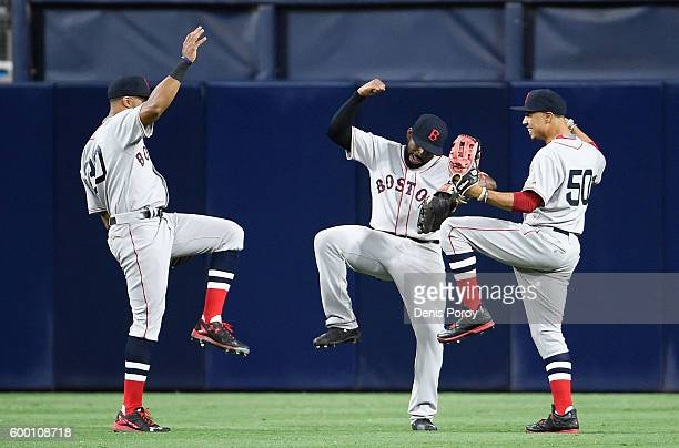 Chris Young of the Boston Red Sox left Jackie Bradley Jr #25 center and Mookie Betts celebrate after beating the San Diego Padres 72 in a baseball...