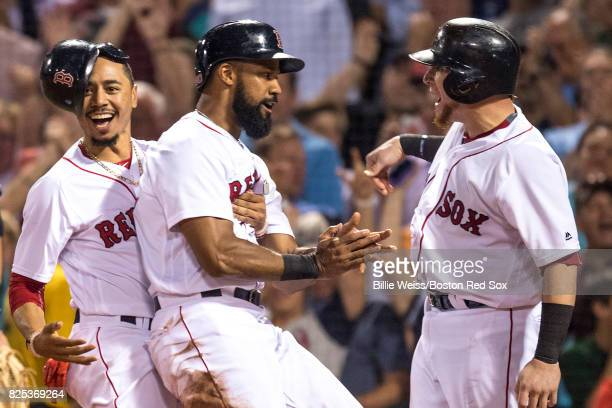 Chris Young of the Boston Red Sox reacts with Mookie Betts and Christian Vazquez after scoring during the sixth inning of a game against the...