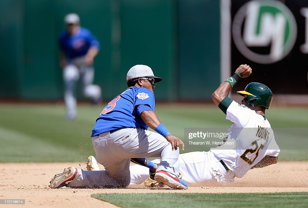 Chris Young #25 of the Oakland Athletics attempting to steal second base is tagged out by Starlin Castro #13 of the Chicago Cubs in the seventh inning at O.co Coliseum on July 4, 2013 in Oakland, California.