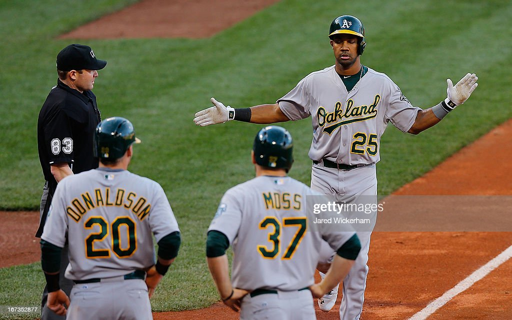 Chris Young #25 of the Oakland Athletics celebrates at home plate with teammates Brandon Moss #37 and Josh Donaldson #20 of the Oakland Athletics after hitting a three-run home run in the fourth inning off of Jon Lester #31 of the Boston Red Sox during the game on April 24, 2013 at Fenway Park in Boston, Massachusetts.