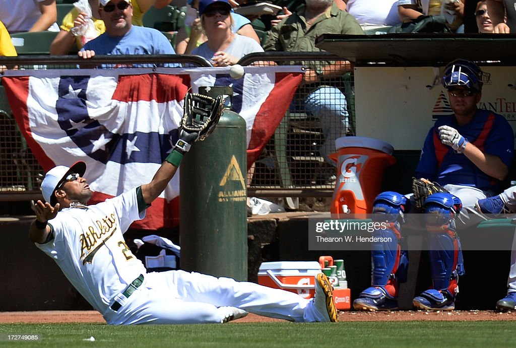 Chris Young #25 of the Oakland Athletics goes into a slide but is unable to make the catch of this foul ball off the bat of Nate Schierholtz #19 of the Chicago Cubs in the seventh inning at O.co Coliseum on July 4, 2013 in Oakland, California.