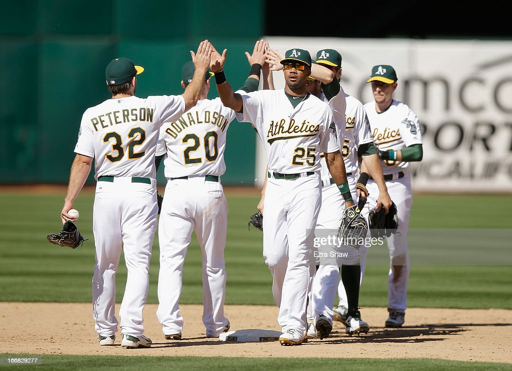 Chris Young #25 of the Oakland Athletics high fives Shane Peterson #32 after the Athletics beat the Houston Astros at O.co Coliseum on April 17, 2013 in Oakland, California.