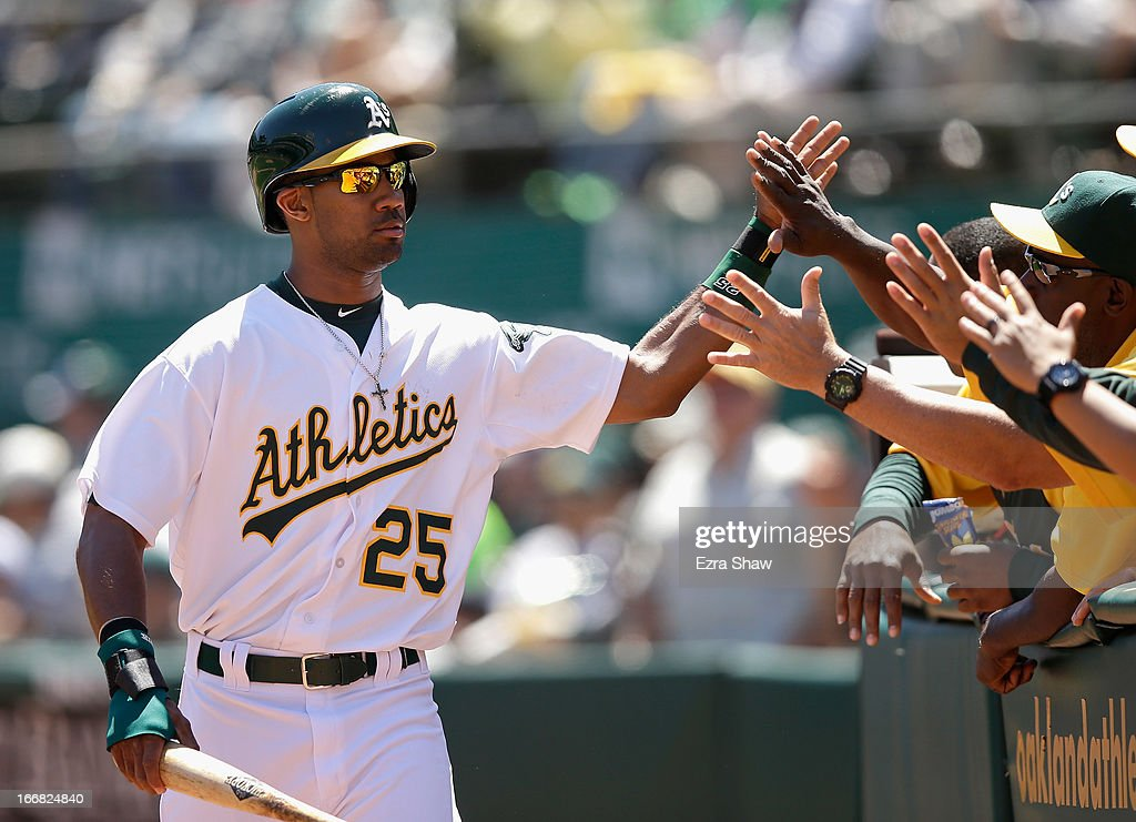 Chris Young #25 of the Oakland Athletics is congratulated by teammates after he scored on a double by Josh Reddick #16 in the first inning of their game against the Houston Astros at O.co Coliseum on April 17, 2013 in Oakland, California.