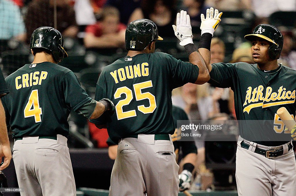 Chris Young #25 of the Oakland Athletics is congrtatulated by <a gi-track='captionPersonalityLinkClicked' href=/galleries/search?phrase=Yoenis+Cespedes&family=editorial&specificpeople=8892047 ng-click='$event.stopPropagation()'>Yoenis Cespedes</a> #52 of the Oakland Athletics and <a gi-track='captionPersonalityLinkClicked' href=/galleries/search?phrase=Coco+Crisp&family=editorial&specificpeople=206376 ng-click='$event.stopPropagation()'>Coco Crisp</a> #4 of the Oakland Athletics after hitting a three run home run in the ninth inning against the Houston Astros at Minute Maid Park on May 24, 2013 in Houston, Texas.