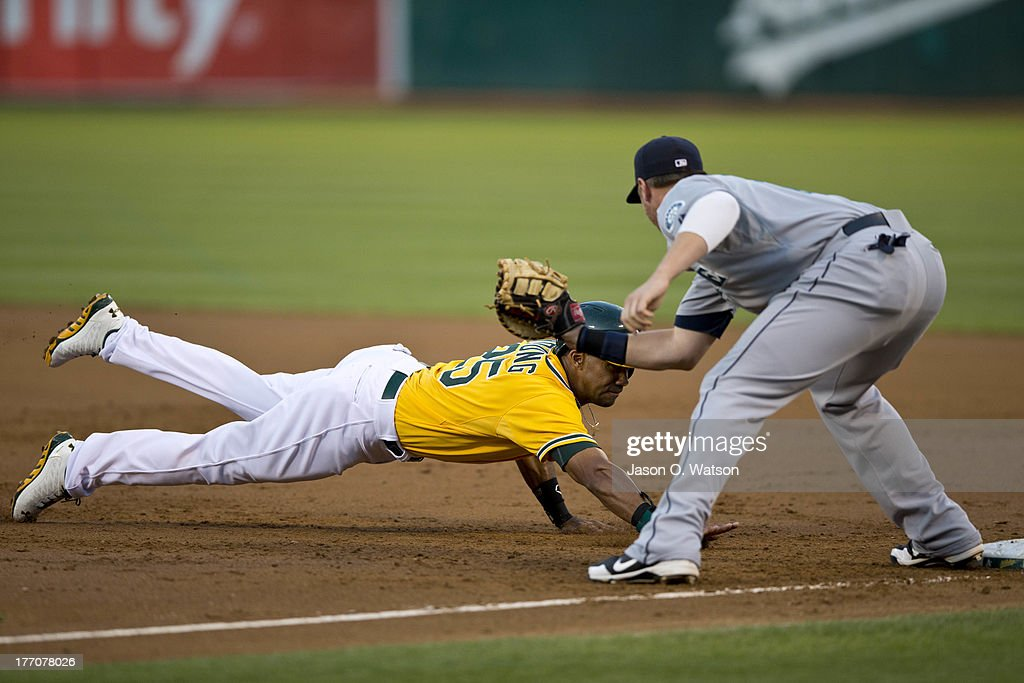 Chris Young #25 of the Oakland Athletics is picked off at first base by <a gi-track='captionPersonalityLinkClicked' href=/galleries/search?phrase=Justin+Smoak&family=editorial&specificpeople=2350583 ng-click='$event.stopPropagation()'>Justin Smoak</a> #17 of the Seattle Mariners during the first inning at O.co Coliseum on August 20, 2013 in Oakland, California.