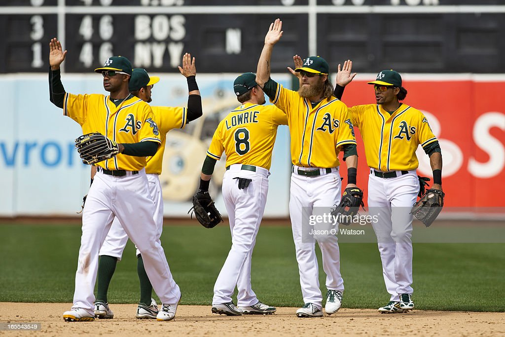 Chris Young #25 of the Oakland Athletics (left), <a gi-track='captionPersonalityLinkClicked' href=/galleries/search?phrase=Josh+Reddick&family=editorial&specificpeople=5746348 ng-click='$event.stopPropagation()'>Josh Reddick</a> #16 (center) and <a gi-track='captionPersonalityLinkClicked' href=/galleries/search?phrase=Coco+Crisp&family=editorial&specificpeople=206376 ng-click='$event.stopPropagation()'>Coco Crisp</a> #4 (right) celebrate with teammates after the game against the Seattle Mariners at O.co Coliseum on April 4, 2013 in Oakland, California. The Oakland Athletics defeated the Seattle Mariners 8-2.
