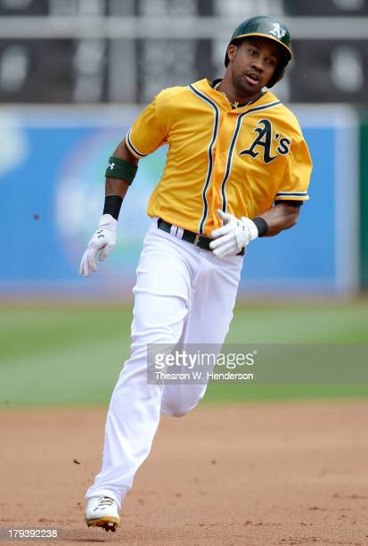 Chris Young of the Oakland Athletics rounds third base attempting to score on a base hit and error when the ball went under the glove of center...