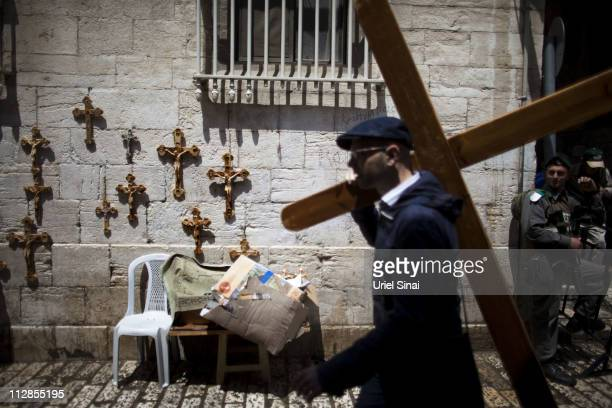 A Chrisitan pilgrim carries a wooden crosses along the Via Dolorosa during the Good Friday procession on April 22 2011 in Jerusalem Israel Thousands...