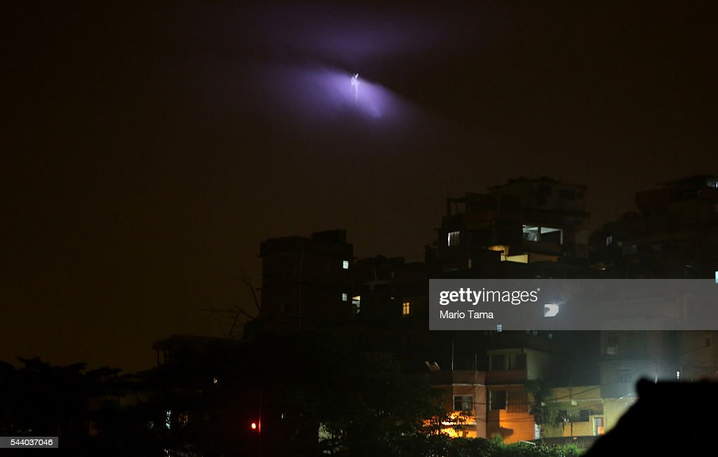 Christ the Redeemer statue is illuminated through the clouds above the Cantagalo 'favela' community on July 1, 2016 in Rio de Janeiro, Brazil. The Rio 2016 Olympic Games commence on August 5.