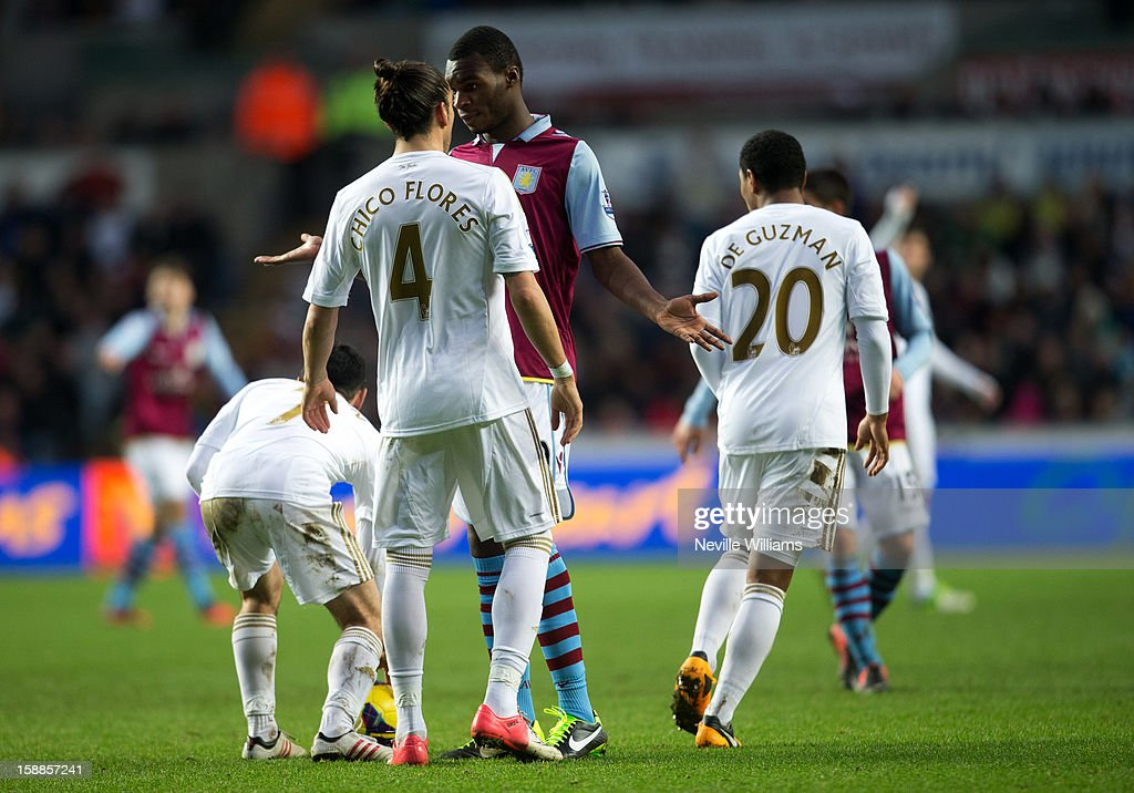 Christain Benteke of Aston Villa exchanges word with Chico Flores of Swansea during the Barclays Premier League match between Swansea City and Aston Villa at Liberty Stadium on January 01, 2013 in Swansea, Wales.