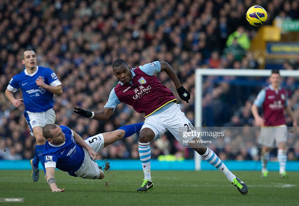 Christain Benteke of Aston Villa is challenged by John Heitinga of Everton during the Barclays Premier League match between Everton and Aston Villa at Goodison Park on February 02, 2013 in Liverpool, England.