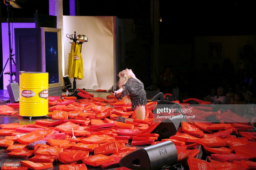 Christelle Chollet performs after the traditional throw of cushions at the final of her one woman show 'The New Show', written and set stage by Remy Caccia at 29th Ramatuelle Festival day 10 on August 9, 2013 in Ramatuelle, France.