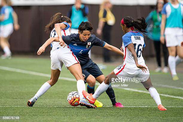 Christen Press and Crystal Dunn of the US Women's National Team double teams Saki Kumagai of Japan during the second half of a friendly match on June...