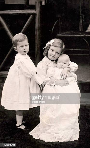 Christening portrait featuring a baby and two young children circa 1910