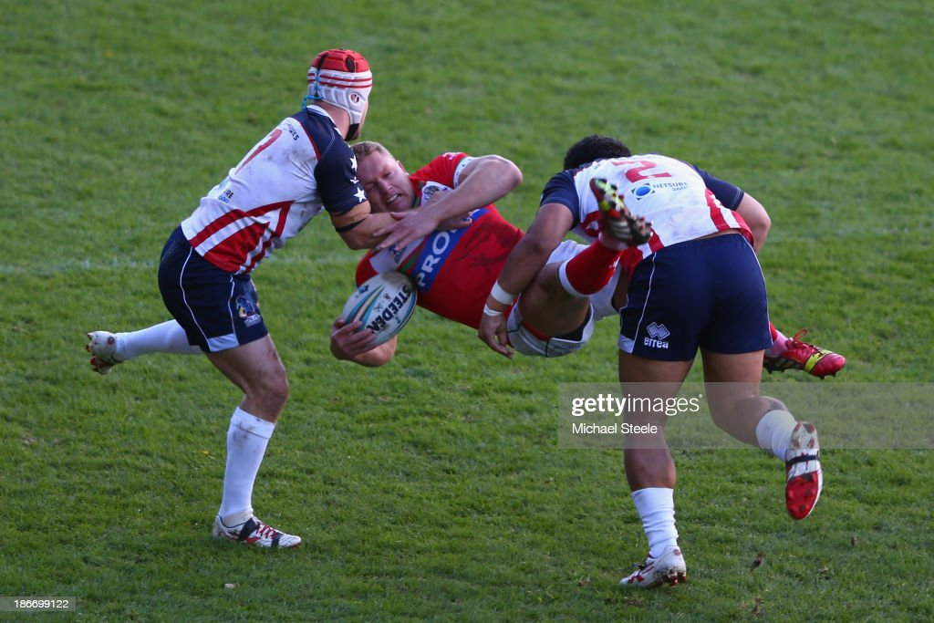 Christiaan Roets of Wales is upended by Craig Priestly and Bureta Faraimo of USA during the Rugby League World Cup Group D match between Wales and...