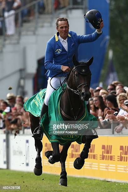 Christian Ahlmann of Germany rides on Codex One and does a lap of honour winning the Rolex Grand Prix jumping competition during the 2014 CHIO Aachen...