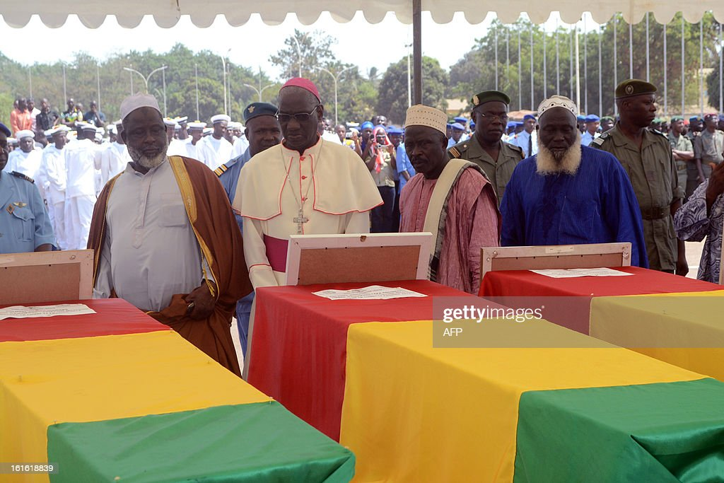Christian and Muslim religious officials pay their respect past the coffins of the victims of a plane carrying a military delegation from Guinea that crashed two days ago in the Liberian town of Charlesville, killing the army chief of staff and 10 other people, during a ceremony in Conakry on February 13, 2013. AFP PHOTO / CELLOU BINANI