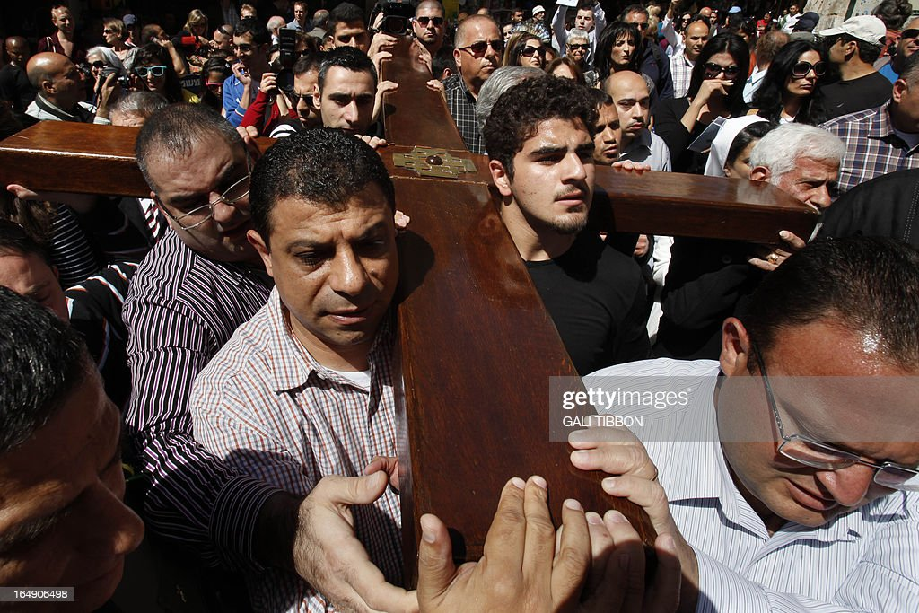 Christian Arab worshipers carry a large wooden cross along the Via Dolorosa (Way of Suffering) as they enter the Church of the Holy Sepulchre in Jerusalem's Old City during the Good Friday procession on March 29, 2013. Thousands of Christian pilgrims took part in processions along the route where according to tradition Jesus Christ carried the cross during his last days.