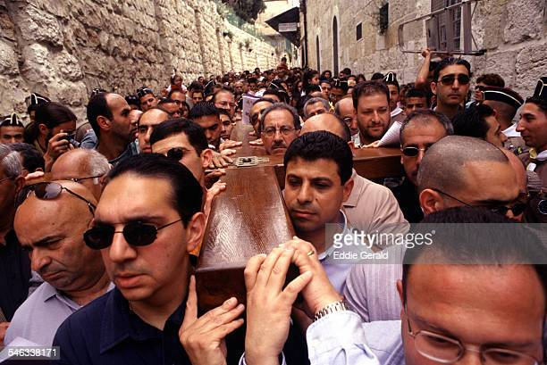 Christian Arab worshippers carry a large wooden cross along the path where Jesus walked now known as the Via Dolorosa on Good Friday in the Old City...