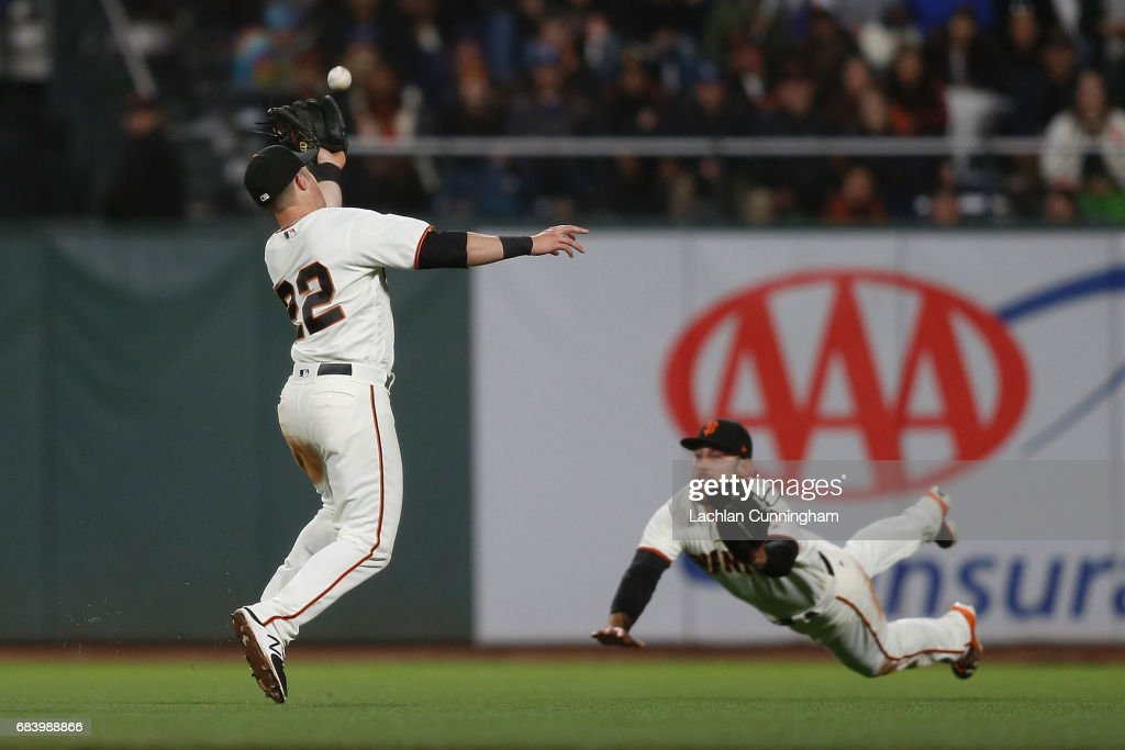 Christian Arroyo #22 and Mac Williamson #51 of the San Francisco Giants fail to catch a fly ball hit by Justin Turner #10 of the Los Angeles Dodgers at AT&T Park on May 16, 2017 in San Francisco, California.