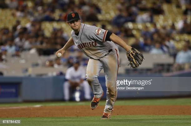 Christian Arroyo of the San Francisco Giants fields a ground ball with his bare hand and throws to first base in the eighth inning during the MLB...