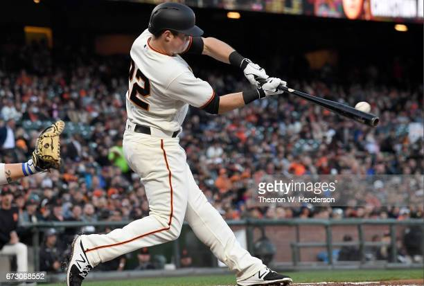 Christian Arroyo of the San Francisco Giants gets a base hit against the Los Angeles Dodgers in the bottom of the first inning at ATT Park on April...
