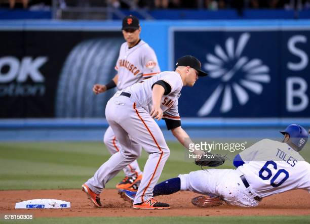 Christian Arroyo of the San Francisco Giants tags out Andrew Toles of the Los Angeles Dodgers on an attempted steal during the first inning at Dodger...