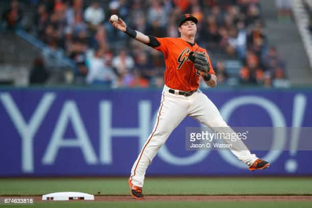 Christian Arroyo of the San Francisco Giants throws to first base after fielding a ground ball hit off the bat of Manuel Margot of the San Diego...