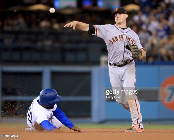 Christian Arroyo of the San Francisco Giants turns a double play over Andrew Toles of the Los Angeles Dodgers to end the ninth inning and send the...