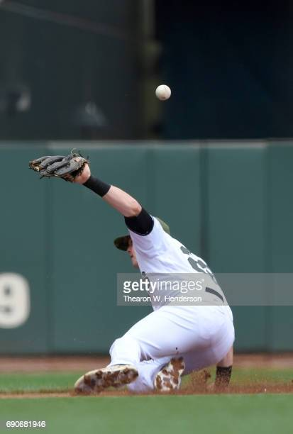 Christian Arroyo of the San Francisco Giants watches the ball kick off his glove for a basehit off the bat of Anthony Rendon of the Washington...
