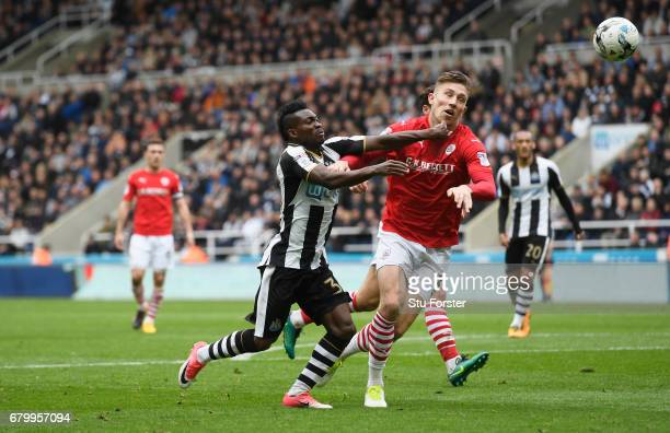 Christian Atsu of Newcastle United and Angus MacDonald of Barnsley battle for possession during the Sky Bet Championship match between Newcastle...