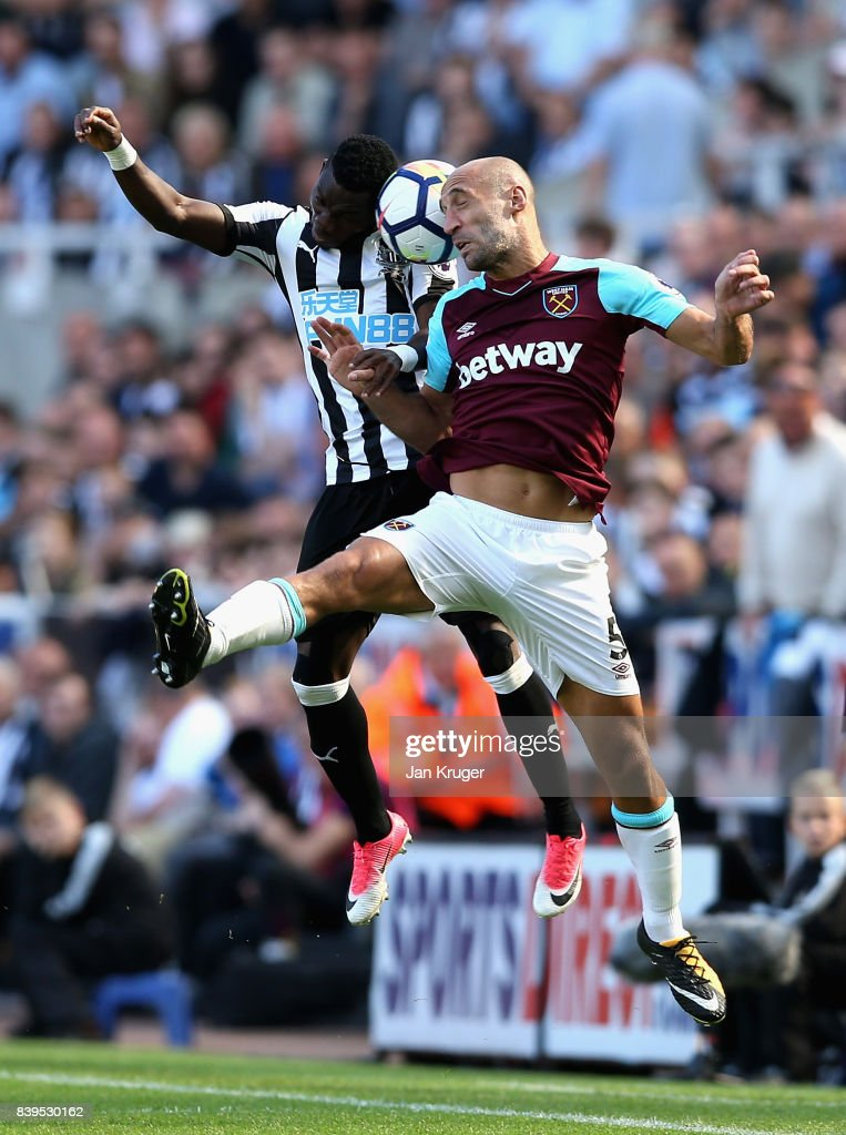 Christian Atsu of Newcastle United and Pablo Zabaleta of West Ham United battle for possession in the air during the Premier League match between Newcastle United and West Ham United at St. James Park on August 26, 2017 in Newcastle upon Tyne, England.
