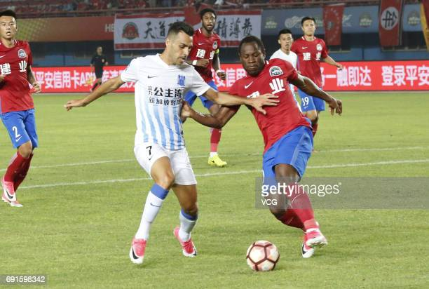 Christian Bassogog of Henan Jianye and Eran Zahavi of Guangzhou RF compete for the ball during the 12th round match of 2017 Chinese Football...