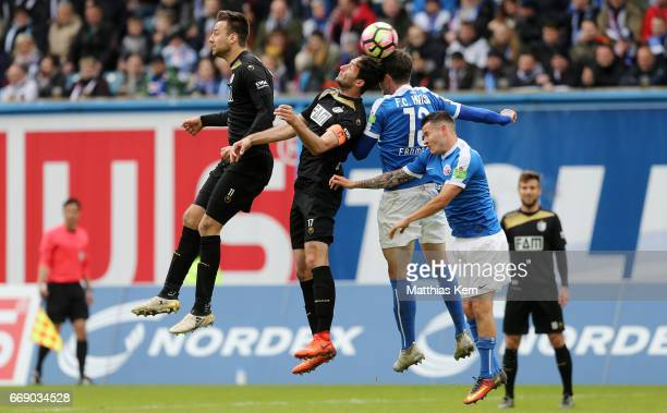 Christian Beck Marius Sowislo Dennis Erdmann and Christopher Quiring jump for a header during the third league match between FC Hansa Rostock and 1FC...