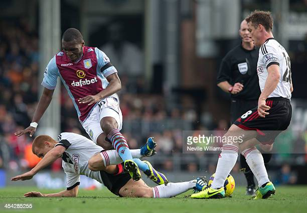 Christian Benteke of AstonVilla is challenged by Steve Sidwell of Fulham during the Barclays Premier League match between Fulham and Aston Villa at...