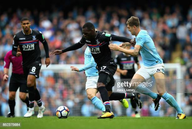 Christian Benteke of Crystal Palace attempts to get past John Stones of Manchester City during the Premier League match between Manchester City and...