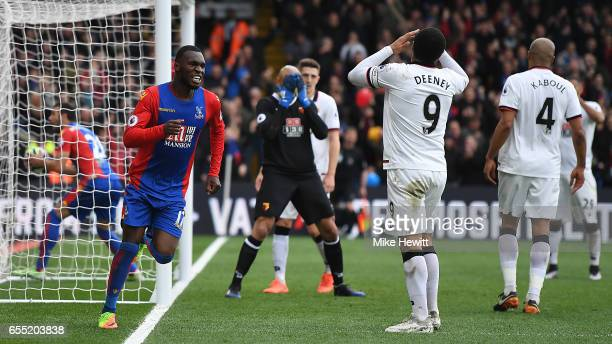 Christian Benteke of Crystal Palace celebrates as Troy Deeney of Watford despairs after scoring an own goal during the Premier League match between...