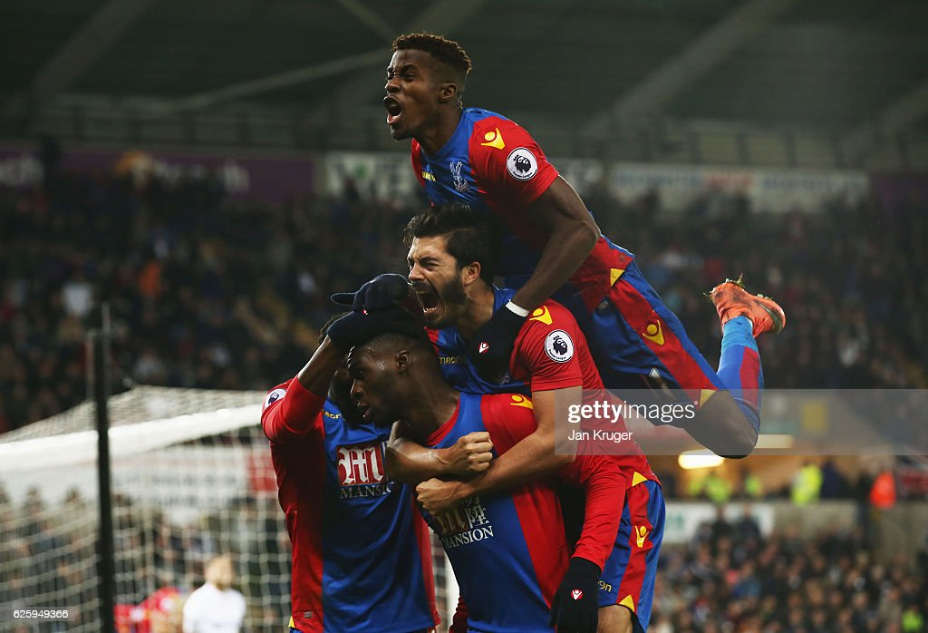 Christian Benteke (2nd L) of Crystal Palace celebrates scoring his team's fourth goal with his team mates incluidng Wilfried Zaha (top) during the Premier League match between Swansea City and Crystal Palace at Liberty Stadium on November 26, 2016 in Swansea, Wales.
