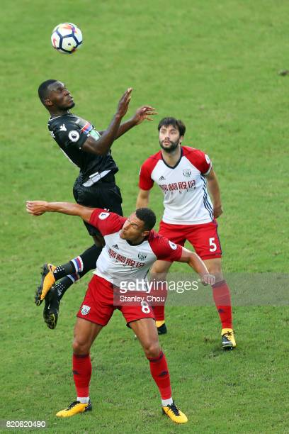 Christian Benteke of Crystal Palace heads clear off Jake Livermore of West Brombich Albion during the Premier League Asia Trophy match between West...