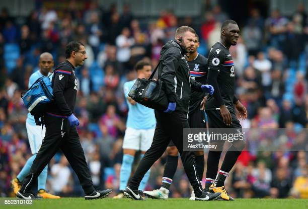 Christian Benteke of Crystal Palace leaves the pitch with medical staffs during the Premier League match between Manchester City and Crystal Palace...