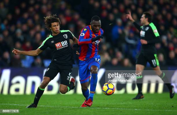 Christian Benteke of Crystal Palace runs with the ball under pressure from Nathan Ake of AFC Bournemouth during the Premier League match between...