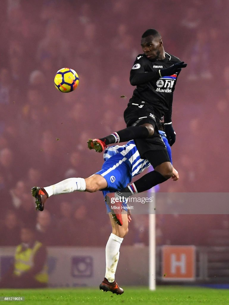 Christian Benteke of Crystal Palace wins a header as a smoke bomb goes off in the away end during the Premier League match between Brighton and Hove Albion and Crystal Palace at Amex Stadium on November 28, 2017 in Brighton, England.